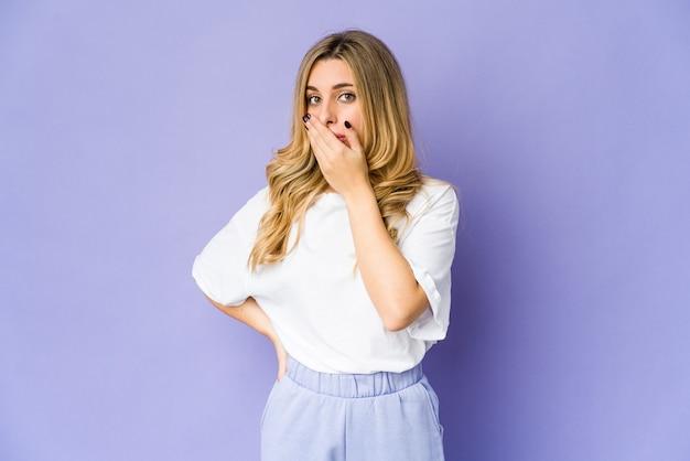 Jonge kaukasische blonde vrouw die mond behandelt met handen die bezorgd kijken.