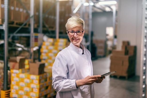 Jonge kaukasische blonde vrouw in wit uniform met behulp van tablet in magazijn. jonge kaukasische blonde vrouw in wit uniform met behulp van tablet in magazijn.