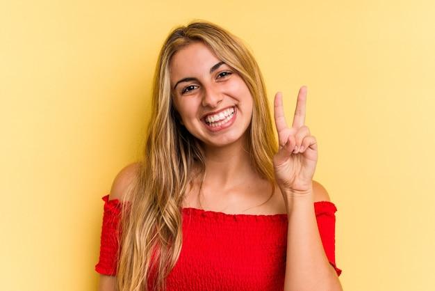 Jonge kaukasische blondevrouw die op gele achtergrond wordt geïsoleerd die overwinningsteken toont en breed glimlacht.