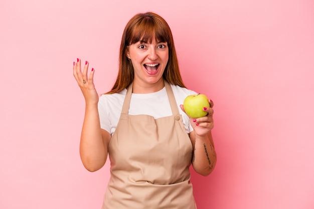 Jonge kaukasische bochtige vrouw die thuis kookt met een appel geïsoleerd op een roze achtergrond die een aangename verrassing ontvangt, opgewonden en handen opsteekt.