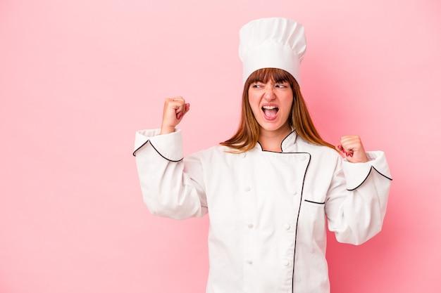 Jonge kaukasische chef-kokvrouw die op roze achtergrond wordt geïsoleerd die vuist opheft na een overwinning, winnaarconcept.