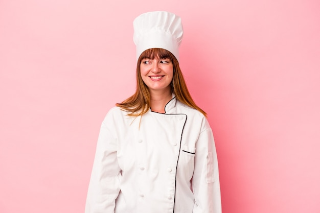 Jonge kaukasische chef-kokvrouw die op roze achtergrond wordt geïsoleerd kijkt opzij glimlachend, vrolijk en aangenaam.