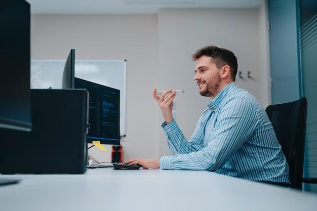 Jonge kaukasische computerman die in het bureau voor een computer werkt