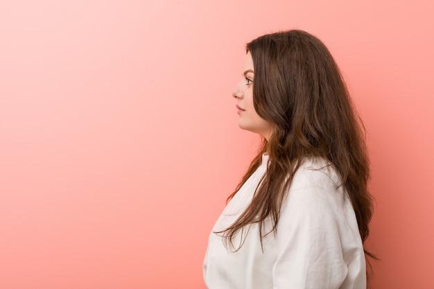 Jonge kaukasische curvy vrouw die zich tegen roze bevindt