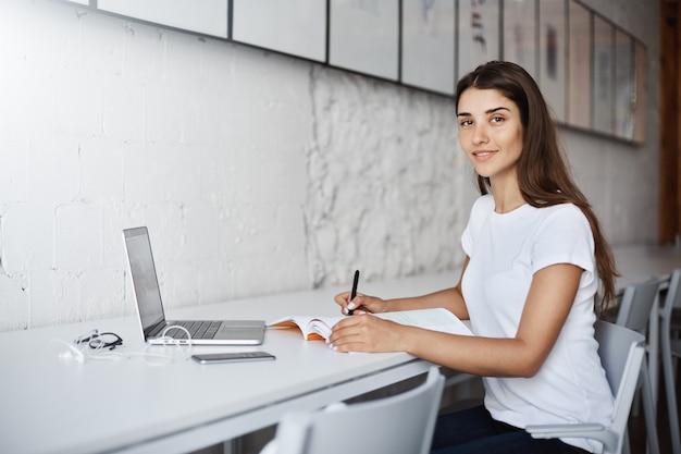 Jonge kaukasische damestudent die camera bekijkt die het lerende boek van het meubeldesign bekijkt. onderwijs concept.