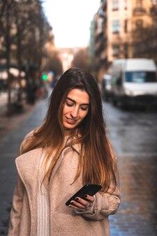 Jonge kaukasische donkerbruine vrouw die een smartphone met behulp van