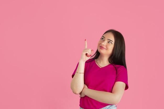 Jonge kaukasische donkerbruine vrouw op roze muur