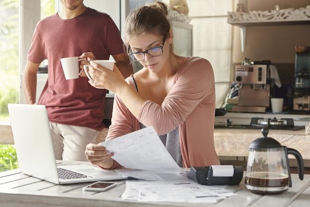 Jonge kaukasische familie rekeningen berekenen, financiën herzien en gezinsbudget samen in de keuken plannen