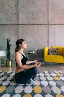 Jonge kaukasische fitness vrouw mediteren, yoga binnenshuis thuis in de buurt van het bed doen. fit en gezond blijven
