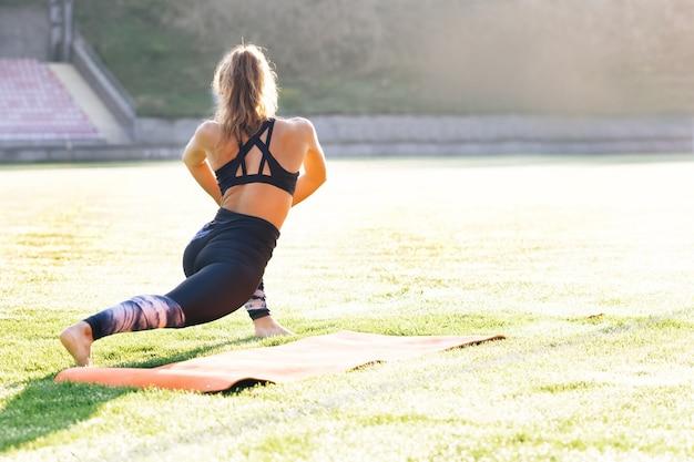 Jonge kaukasische fitte sportvrouw die haar lichaam uitrekt voordat ze gaat trainen buiten het meisje in de sport