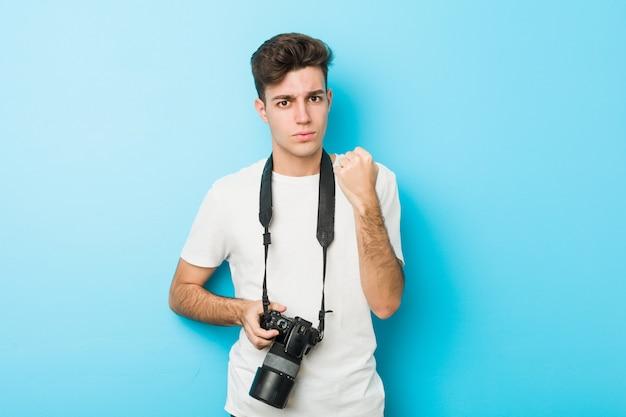 Jonge kaukasische fotograafmens die een camera houden die vuist tonen aan camera, agressieve gelaatsuitdrukking.