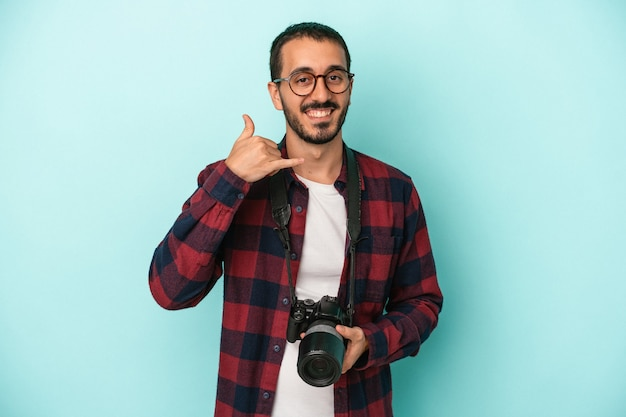 Jonge kaukasische fotograafmens die op blauwe achtergrond wordt geïsoleerd die een mobiel telefoongesprekgebaar met vingers toont.