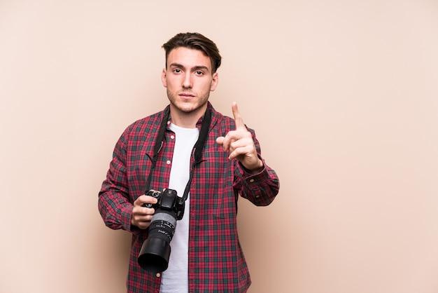 Jonge kaukasische geïsoleerde fotograafmens die nummer één met vinger toont.