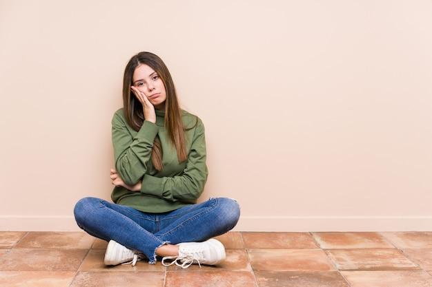 Jonge kaukasische geïsoleerde vrouwenzitting op de vloer die zich verveelt, vermoeid en behoefte heeft aan een ontspannen dag.