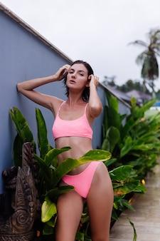 Jonge kaukasische geschikte slanke gebruinde donkerbruine vrouw in roze heldere bikini buiten het tropische blad van de villa