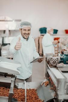 Jonge kaukasische glimlachende supervisor die de kwaliteit van voedsel in voedselplant evalueert terwijl hij tablet vasthoudt en duimen opdagen. de mens is gekleed in wit uniform en heeft haarnet.
