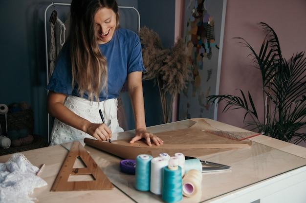 Jonge kaukasische glimlachende vrouw die een patroon voor doek meet. op maat concept. naaien bedrijfsconcept.