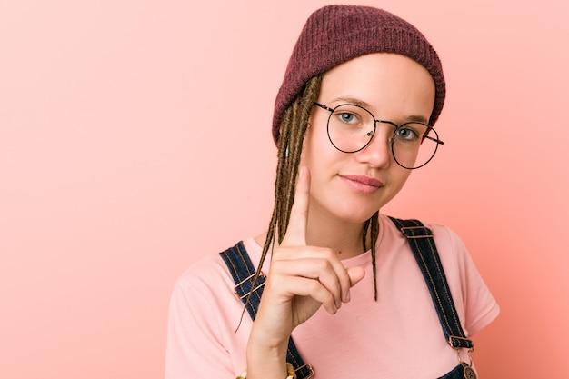 Jonge kaukasische hipstervrouw die nummer één met vinger tonen.