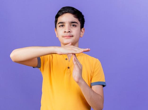 Jonge kaukasische jongen die camera bekijkt die time-outgebaar doet dat op purpere achtergrond met exemplaarruimte wordt geïsoleerd