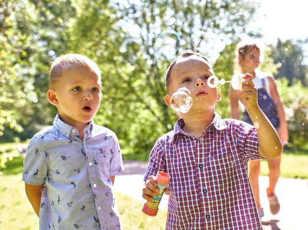 Jonge kaukasische jongen die de zeepbels op aard blaast.