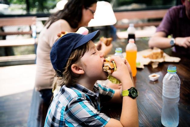 Jonge kaukasische jongen die hamburger eet