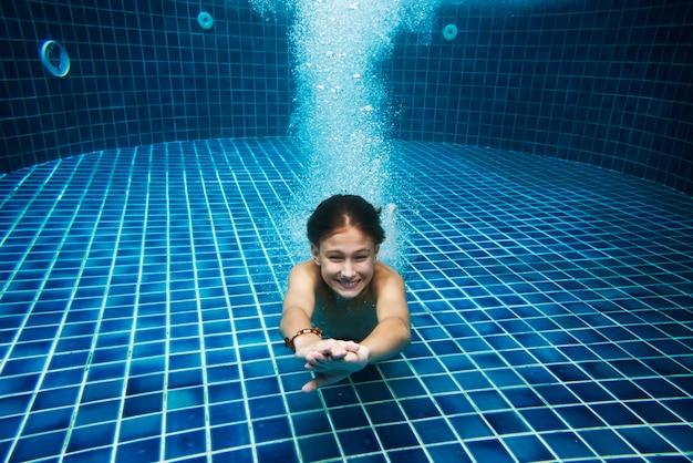 Jonge kaukasische jongen die van de pool geniet onderwater