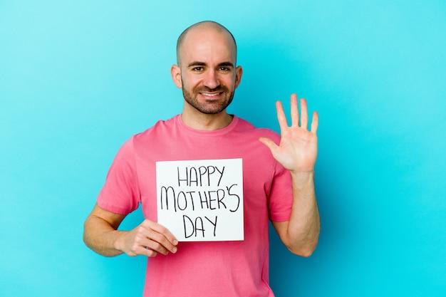 Jonge kaukasische kale mens die een gelukkig aanplakbiljet van de moederdag houdt dat op blauwe muur wordt geïsoleerd die vrolijk toont die nummer vijf met vingers toont