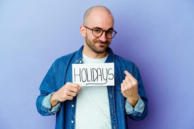 Jonge kaukasische kale mens die een vakantieplakkaat houdt dat op blauwe muur wordt geïsoleerd die met vinger naar u richt alsof uitnodigend kom dichterbij.