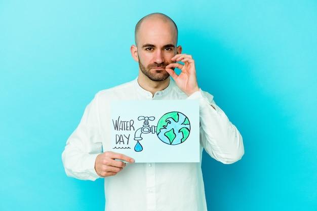 Jonge kaukasische kale mens die wereldwaterdag viert die op blauwe achtergrond met vingers op lippen wordt geïsoleerd die een geheim houden. Premium Foto