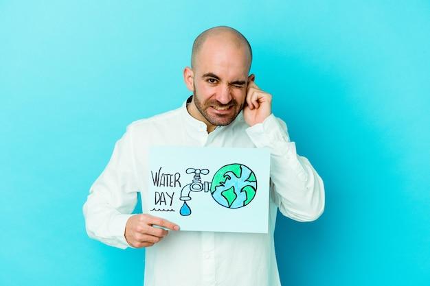Jonge kaukasische kale mens die wereldwaterdag viert die op blauwe achtergrond wordt geïsoleerd die oren behandelt met handen.