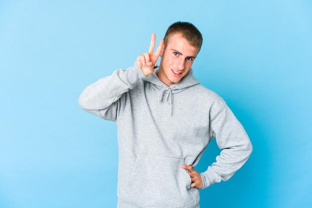 Jonge kaukasische knappe mens die nummer twee met vingers toont.