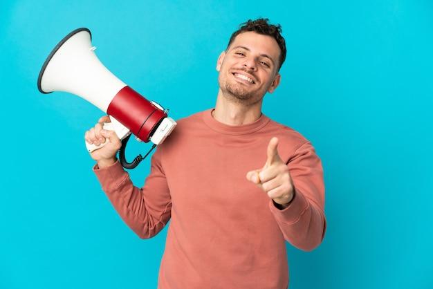 Jonge kaukasische knappe mens die op blauwe muur wordt geïsoleerd die een megafoon houdt en glimlacht terwijl hij naar voren wijst