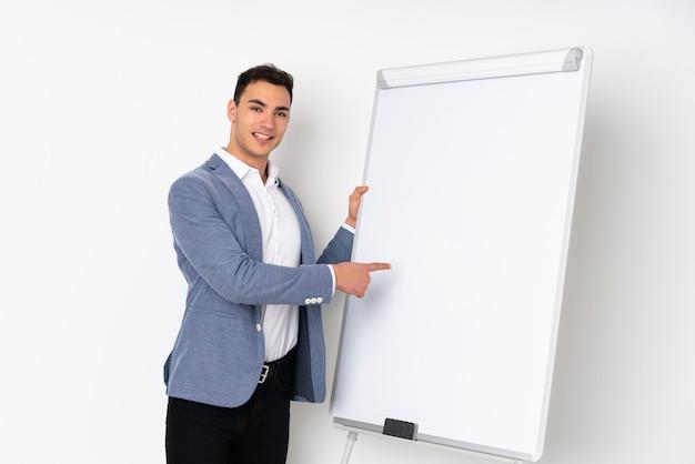 Jonge kaukasische knappe mens op purpere muur die een presentatie op wit bord geeft en daarin schrijft