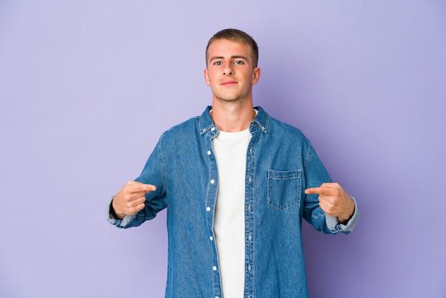 Jonge kaukasische knappe mensenpersoon die met de hand naar de ruimte van een overhemdskopie wijst, trots en zelfverzekerd