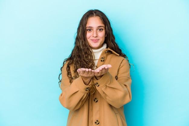 Jonge kaukasische krullende haarvrouw die iets met palmen houdt