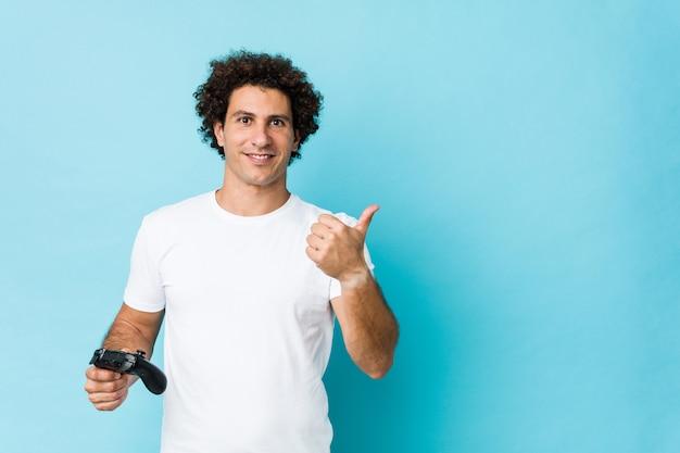 Jonge kaukasische krullende mens die een spelcontrolemechanisme houdt die en duim tegenhoudt opheft