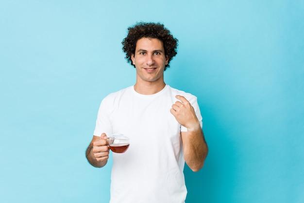 Jonge kaukasische krullende mens die een theekop houdt die met vinger naar u richt alsof uitnodigend kom dichterbij.