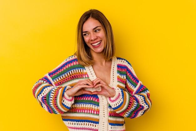 Jonge kaukasische magere vrouw die op geel wordt geïsoleerd dat en een hartvorm met handen glimlacht toont.