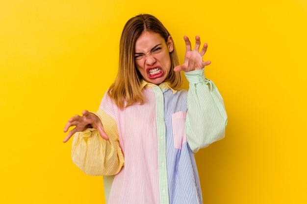 Jonge kaukasische magere vrouw die op geel wordt geïsoleerd dat klauwen toont die een kat, agressief gebaar imiteren.