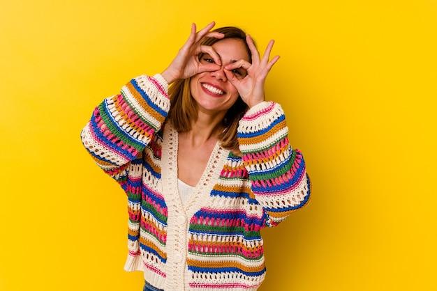 Jonge kaukasische magere vrouw die op geel wordt geïsoleerd dat ok teken over ogen toont