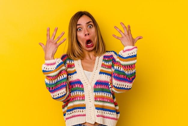 Jonge kaukasische magere vrouw die op geel wordt geïsoleerd die nummer tien met handen toont.
