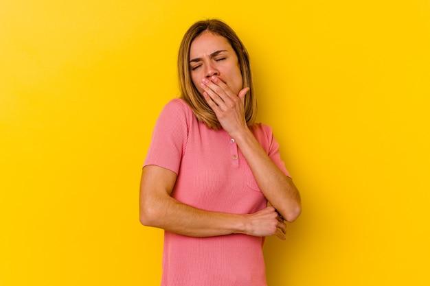 Jonge kaukasische magere vrouw die op gele geeuw wordt geïsoleerd die een moe gebaar toont dat mond behandelt met hand.