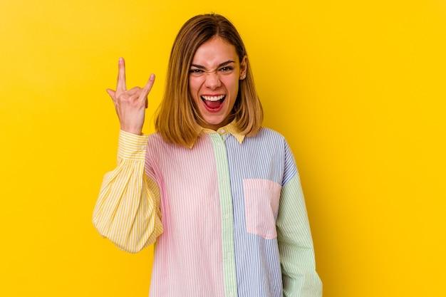 Jonge kaukasische magere vrouw die rotsgebaar met vingers toont
