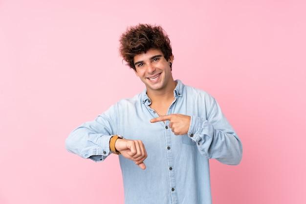 Jonge kaukasische man over geïsoleerde roze muur die het handhorloge toont