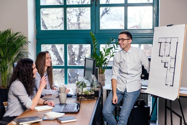 Jonge kaukasische mannelijke architect die de bouwplannen op nieuw huis tonen aan zijn vrouwelijke medewerkers in het modieuze bureau.