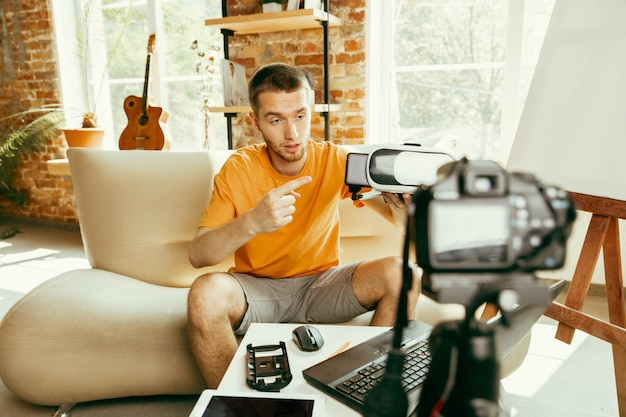 Jonge kaukasische mannelijke blogger die met professionele apparatuur videoreview van vr-bril thuis opnemen. bloggen, videoblog, vloggen. man evalueert virtual reality-headset tijdens live streaming.