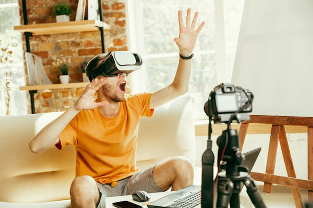 Jonge kaukasische mannelijke blogger die met professionele apparatuur videoreview van vr-bril thuis opnemen.