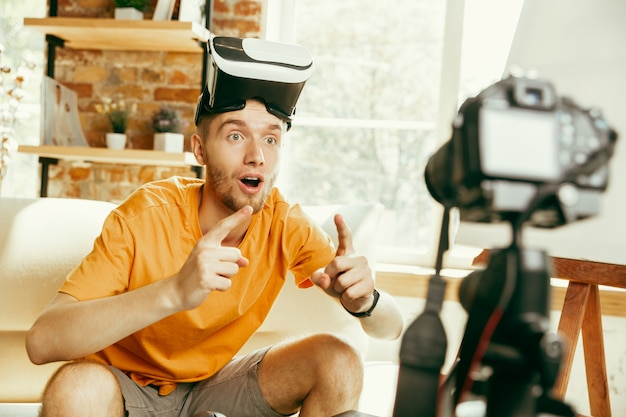 Jonge kaukasische mannelijke blogger met professionele apparatuur die videoreview van vr-bril opneemt
