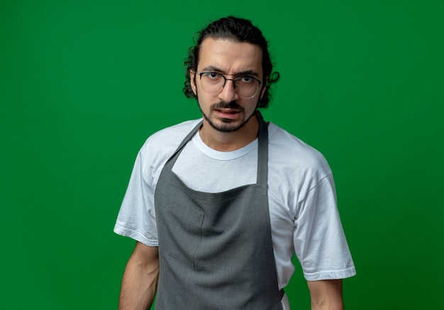 Jonge kaukasische mannelijke kapper die eenvormig en glazen draagt ?? die en camera bekijkt die op groene achtergrond met exemplaarruimte wordt geïsoleerd