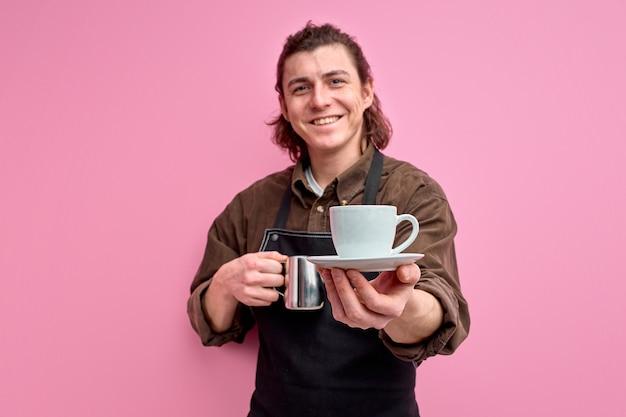 Jonge kaukasische mannelijke ober die kop van koffie aanbiedt die op roze muur wordt geïsoleerd Premium Foto